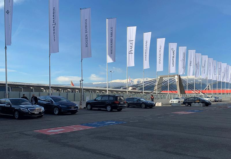 エクジビジョン参加ブランドの旗が、晴天の中に映えるスイス山脈をバックに整然と並んでいます。